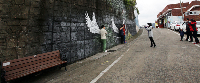 Visitors take a picture against a wall painting of feathers in the Dongpirang Village.